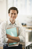Businessman With Files Standing By Cubicle Royalty Free Stock Photography