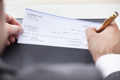 Businessman filling blank cheque Stock Photos