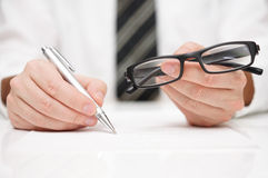 Businessman is filling document and holding reading glasses Stock Photo