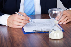 Businessman Filling Form In Front Of Hourglass Royalty Free Stock Photos