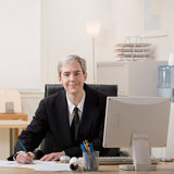 Businessman filling out paperwork at desk. Confident businessman filling out paperwork at desk Royalty Free Stock Image
