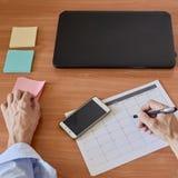 Businessman filling timesheet. Closeup photo of businessman filling weekly time sheet. in French Royalty Free Stock Image