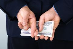 Businessman with finger crossed holding banknotes Stock Photo