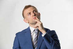Businessman with finger on lips thinking Stock Images