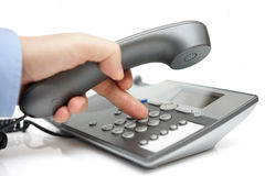 Businessman finger pressing a number button on the land line tel. Ephone Royalty Free Stock Photo