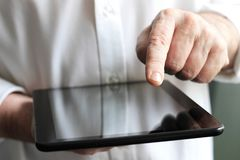 Businessman with finger touching screen of a digital tablet whilst stock images