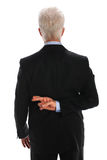 Businessman With Fingers Crossed. Mature businessman with fingers crossed behind back isolated over white background Stock Photo