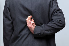 Businessman fingers crossed behind his back royalty free stock images