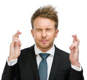 Businessman with fingers crossed and eyes closed. Half-length portrait of businessman with fingers crossed and eyes closed, isolated on white Royalty Free Stock Photos