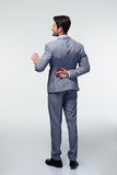 Businessman with fingers crossed. Full length portrait of a businessman with fingers crossed behind back over gray background Royalty Free Stock Photos