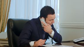 Businessman finish calling and start working with documents in office royalty free stock images