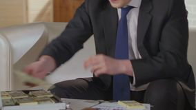 Businessman finishing call on cell phone, putting wads of dollars into suitcase. Stock footage stock footage