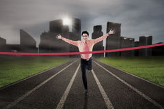 Businessman finish the race. Businessman is finishing the race on city background Stock Photo