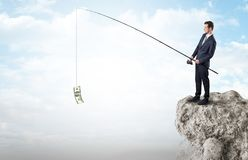 Businessman fishing dollar from a rock Royalty Free Stock Images