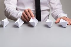 Businessman with five origami paper boats. Businessman sitting at his desk with five origami paper boats in front of him stock images