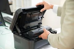 Businessman fixing cartridge in photocopy machine. Close-up Of Businessman Fixing Cartridge In Photocopy Machine In Office Stock Image