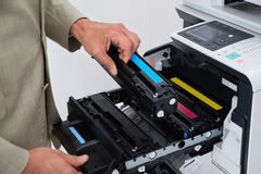 Businessman Fixing Cartridge In Photocopy Machine. Cropped image of businessman fixing cartridge in photocopy machine at office Royalty Free Stock Images