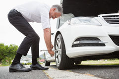Businessman fixing tire Royalty Free Stock Photo