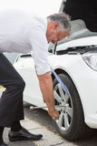 Businessman fixing tire Stock Photo