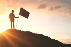 Success and victory concept. Businessman with flag standing on abstract mountain top. Success and victory concept royalty free stock photos