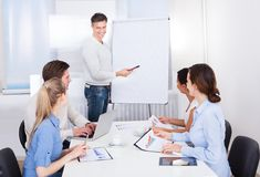 Businessman with flipchart and colleagues Royalty Free Stock Photos