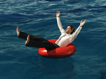 Businessman floating on lifebuoy Stock Photography