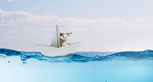 Businessman floating in paper ship . Mixed media Royalty Free Stock Images