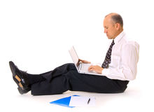 Businessman on the floor with laptop. Businessman sitting on the floor with laptop and documents Stock Photography