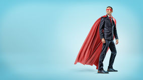 A businessman in a flowing red superhero cape and a mask looking over his shoulder on blue background. Business hero. Business and success. Superpowers Royalty Free Stock Images