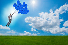 The businessman flying balloons on bright day Royalty Free Stock Photo