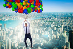 The businessman flying on balloons in challenge concept Stock Photo