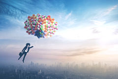 Businessman flying with balloons over the city Stock Photos