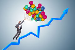 The businessman flying on balloons over graph Stock Photos