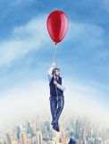 Businessman flying on the big ballon. Above the city stock image