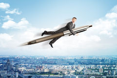 Businessman flying on big pen Stock Photos