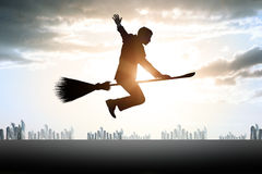 Businessman flying on broom Stock Images