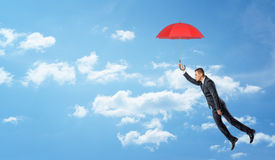 A businessman flying in the clouded sky and holding a red open umbrella. Stock Photo