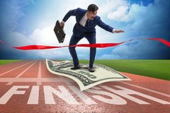 The businessman flying on dollar banknote towards finish line. Businessman flying on dollar banknote towards finish line Royalty Free Stock Images