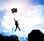 Businessman flying with dollar sign balloons. Silhouette of a businessman crossing a void flying with dollar sign balloons. Cityscape in the background. Mock up Royalty Free Stock Images