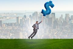 The businessman flying on dollar sign inflatable balloon. Businessman flying on dollar sign inflatable balloon Royalty Free Stock Photography