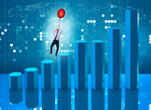 The businessman flying on hot balloon over graph Royalty Free Stock Photos