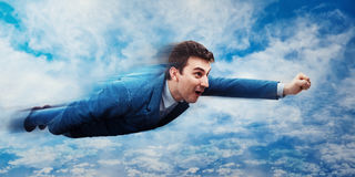 Businessman flying like a superhero. Wondered businessman flying above the clouds like a superhero. Business success, opportunity and risk concept stock photography
