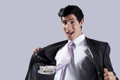 Businessman with a flying necktie with money. Businessman showing money in his flying necktie (isolated on gray Stock Photography