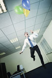 Businessman flying in office with balloons Royalty Free Stock Photo