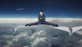 Businessman flying on paper planes Stock Photos