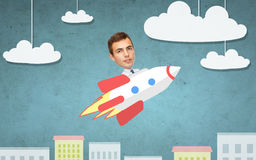 Businessman flying on rocket above cartoon city Stock Image