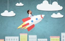 Businessman flying on rocket above cartoon city Royalty Free Stock Photo