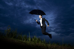 Businessman flying with umbrella Royalty Free Stock Images