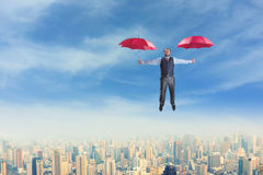 Businessman flying with umbrellas Royalty Free Stock Image