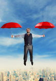 Businessman flying with umbrellas Royalty Free Stock Photos